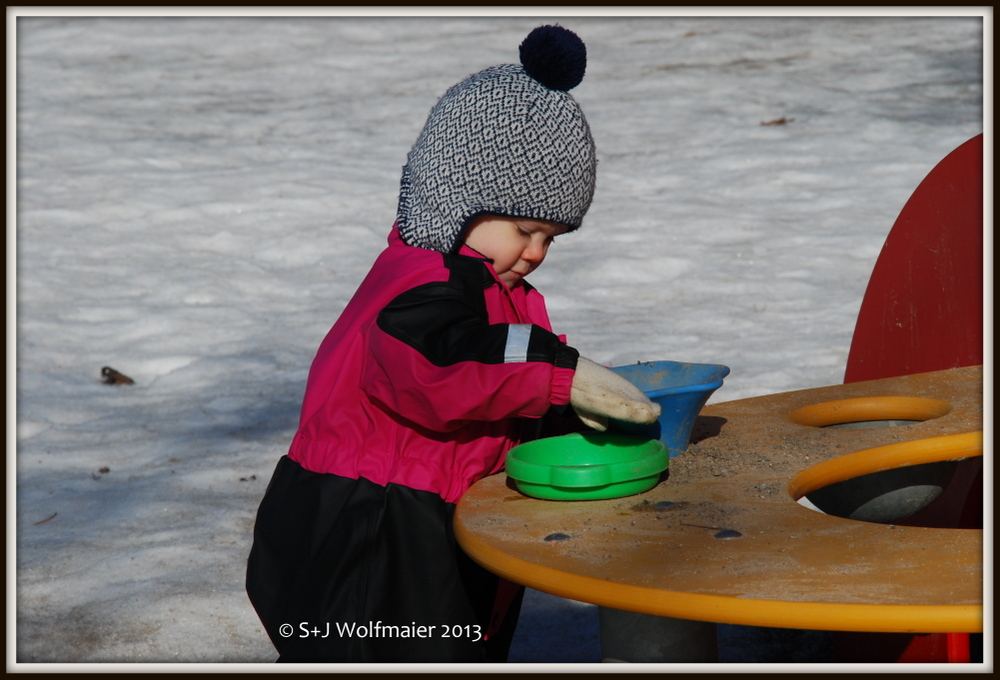 Our daughter playing in the snow, with sand. She is now really enjoys playing at the playground.